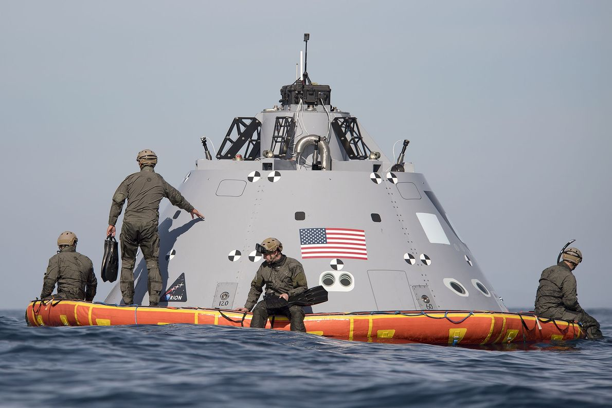U.S. Navy divers assist NASA as they recover a mock-up Orion capsule from the waters off ...