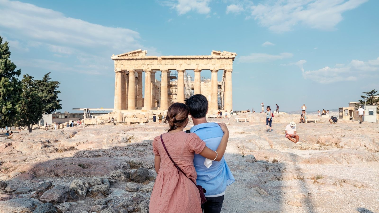 A couple visits the Acropolis in Athens, Greece. The columned Parthenon is usually surrounded by tourist ...