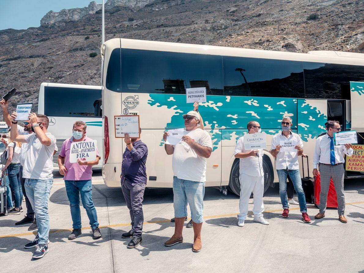 Tour guides with signs and face masks wait at the port in Santorini's capital, Fira. The ...