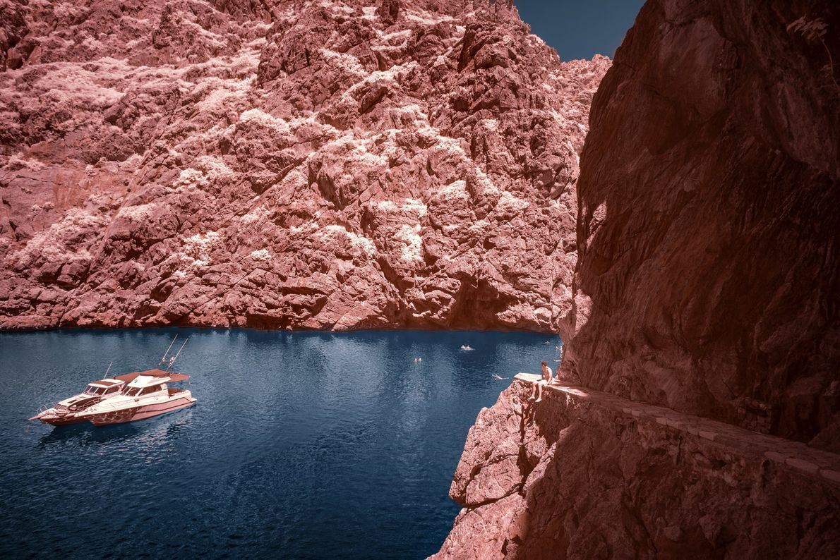 Boats glide through the cove of Sa Calobra, which sits at the end of the Torrent ...