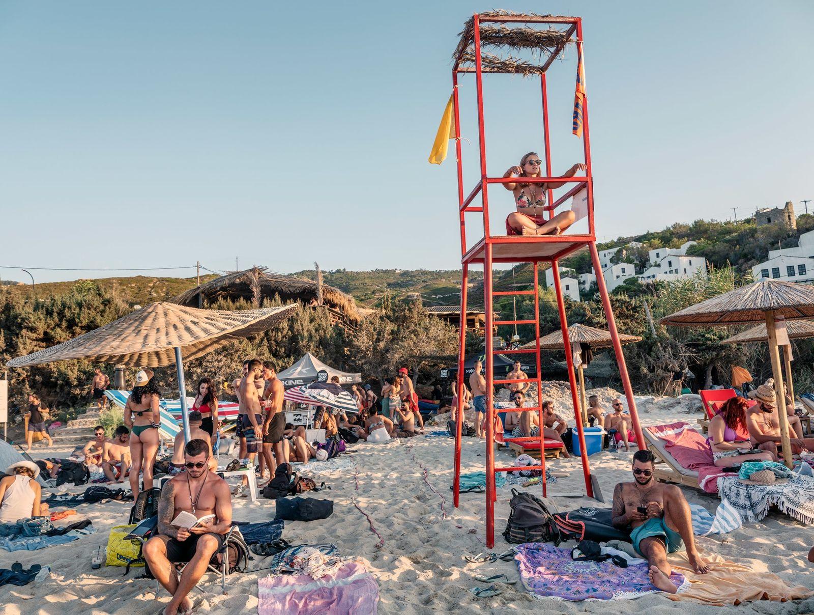 People soak in the sun at Mesakti Beach on the island of Ikaria, Greece.