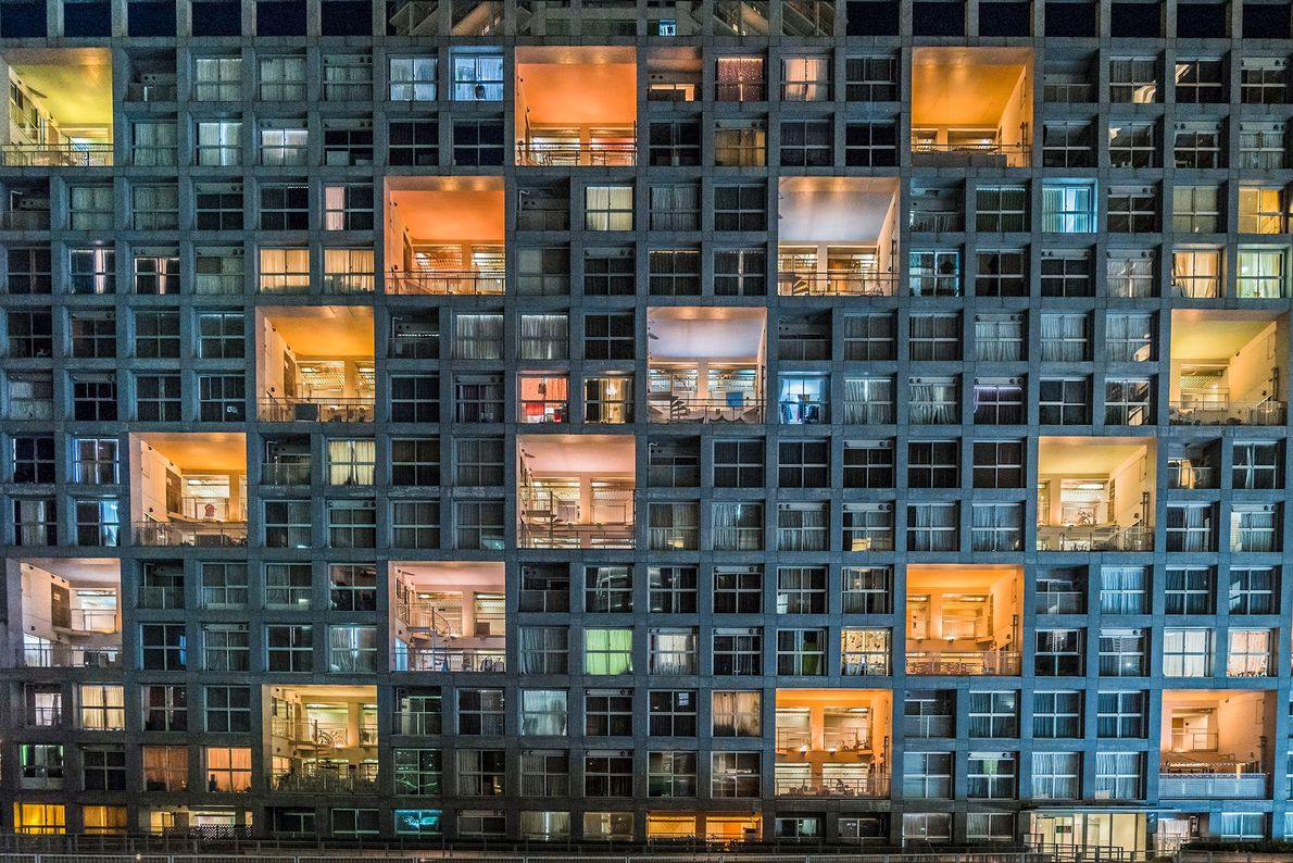 Colorful lights contrast with the dark windows of an apartment building along Tokyo Bay in Japan. ...