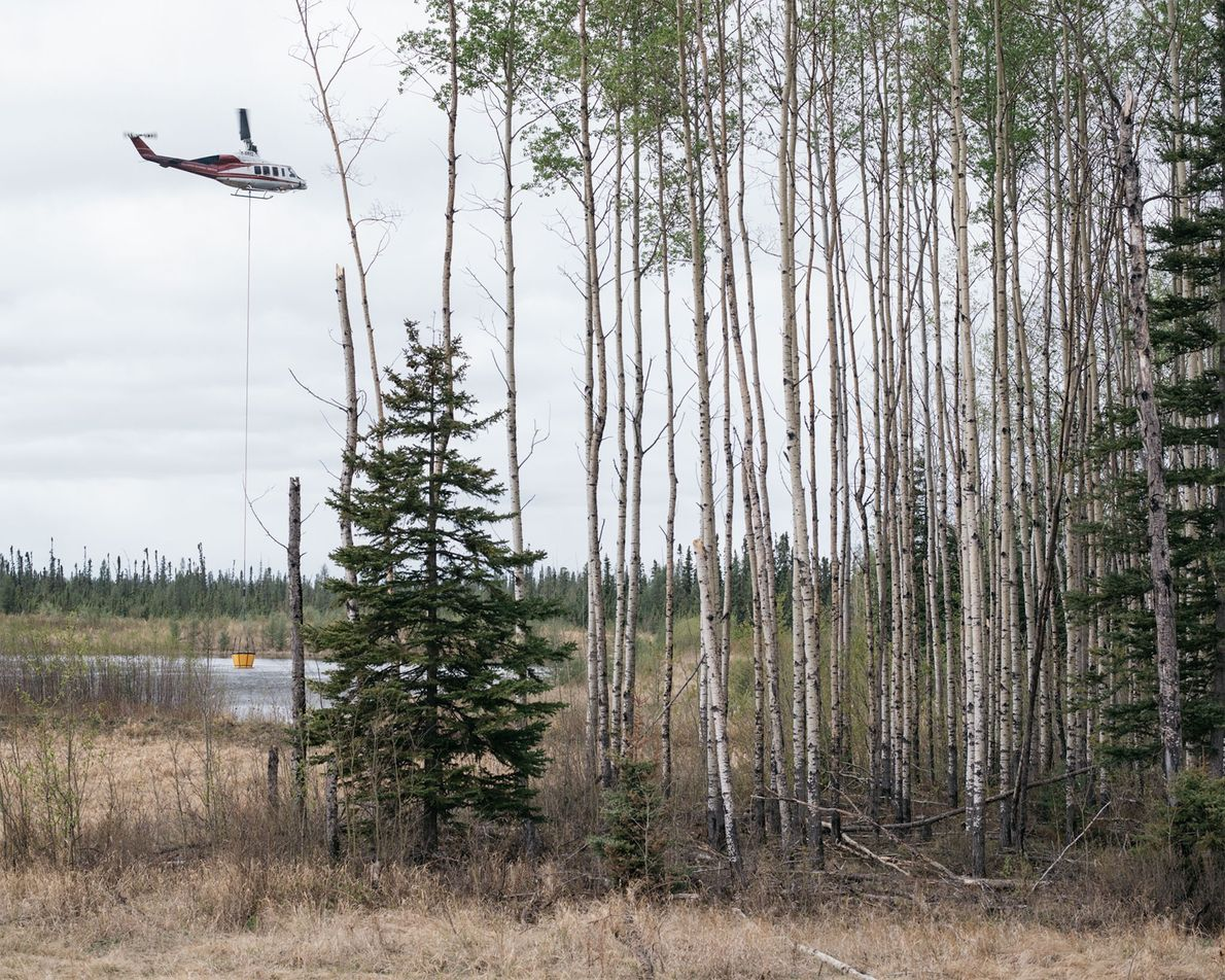 A helicopter collects water to fight the wildfire outside Fort McMurray, Alberta.