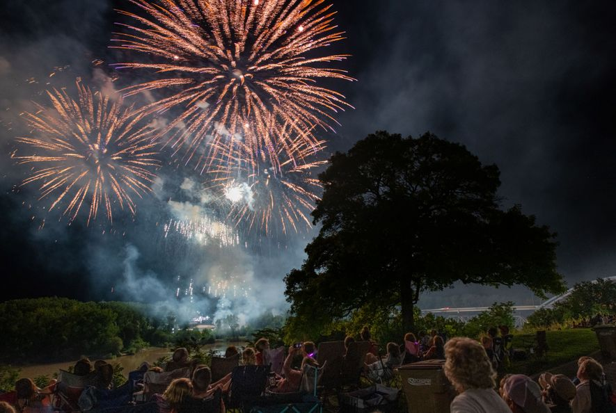 Fireworks explode during the Amelia Earhart Festival in Atchison, Kansas, while spectators watch from the lawn ...