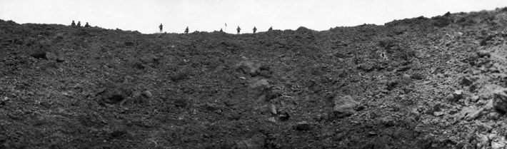 Dwarfed by destruction, Allied soldiers look down into a blast crater made by a mine during ...