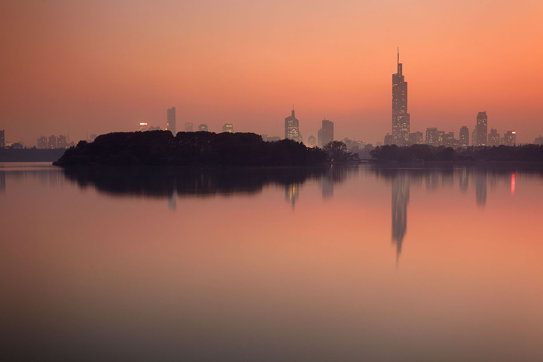 The setting sun frames the Nanjing skyline towering over Ziwu Lake in China.