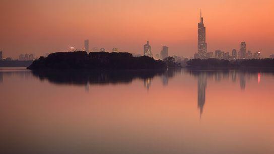 The setting sun frames the Nanjing skyline towering over Ziwu Lake in China.