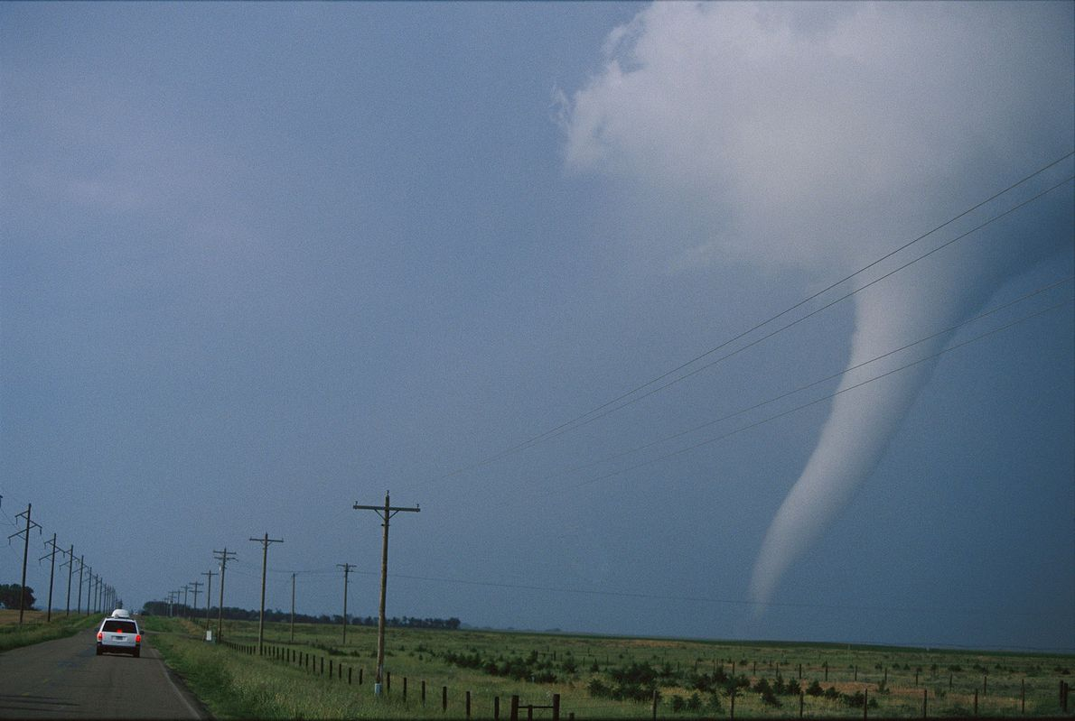 "Tornado chasers in a van track an ""elephant's trunk"" tornado in South Dakota. Storm chaser Tim ..."
