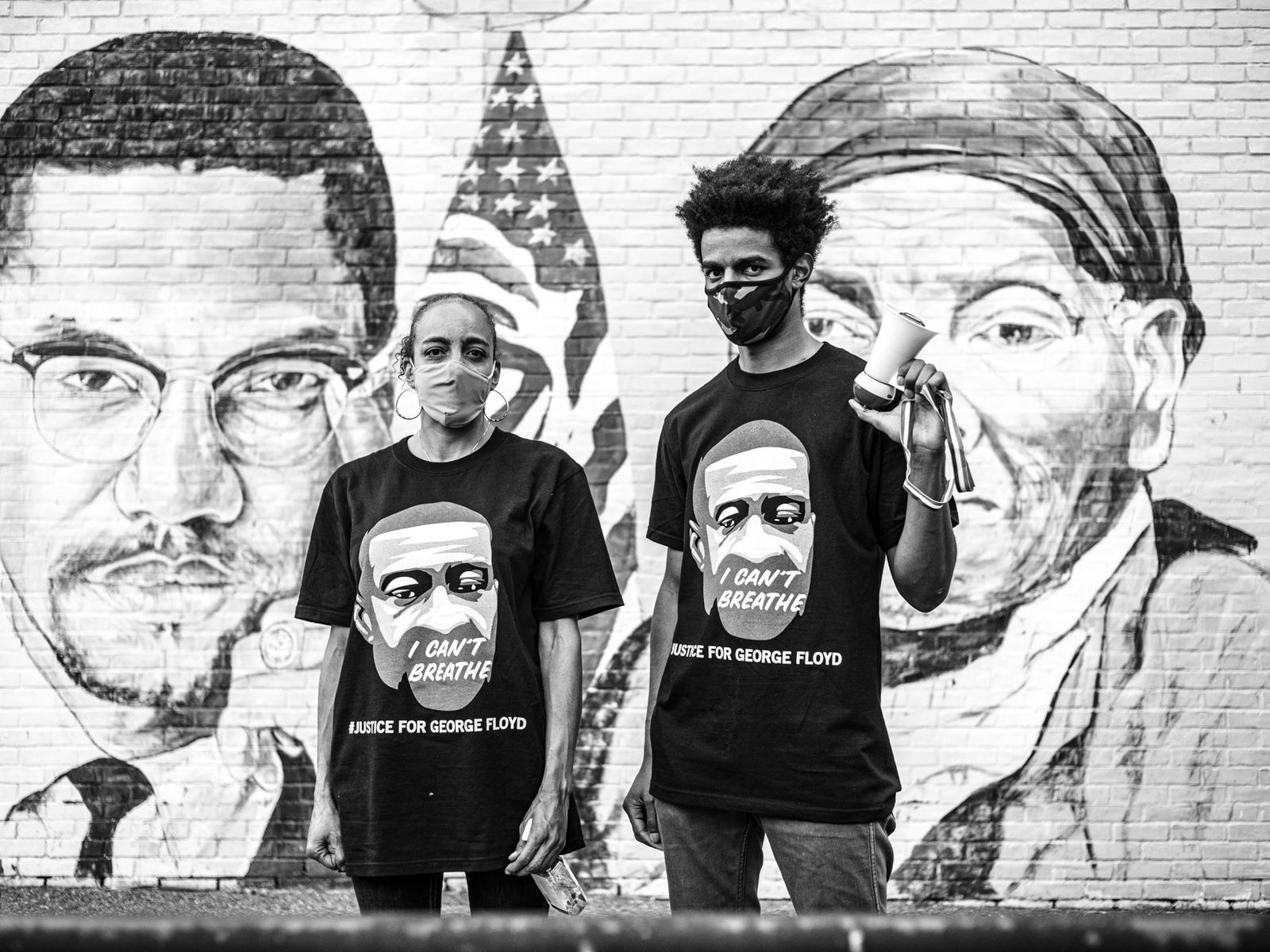 Nicole Harney (left) and her son, Justin, stand in front of a mural of Malcolm X ...