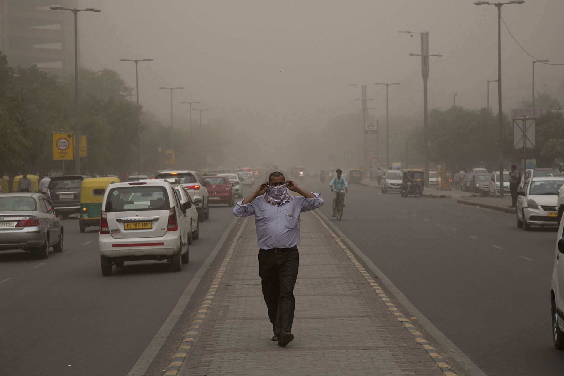 A man wraps a scarf around his nose as a dust storm envelops the city in ...