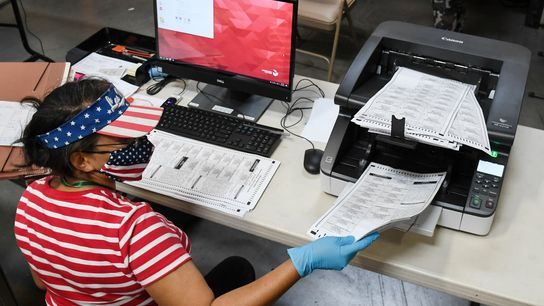 An election worker scans mail-in ballots at the Clark County Election Department on October 20, 2020, ...