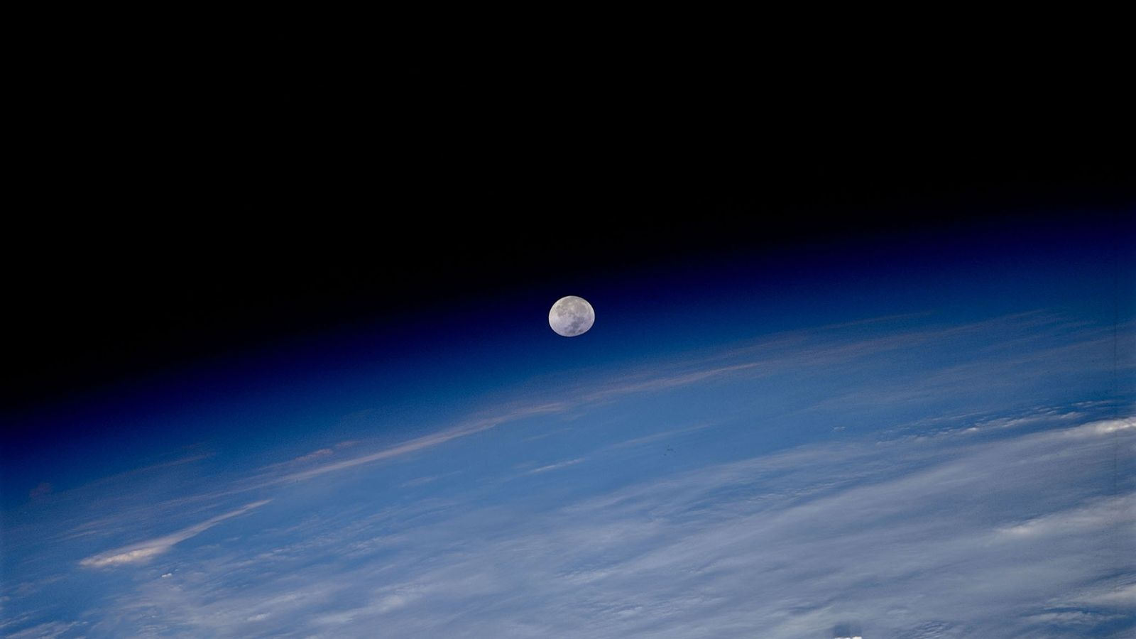 The moon seems to hang in the balance between Earth's atmosphere and the blackness of space ...