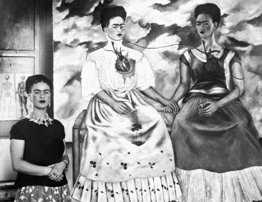 """Frida Kahlo stands next to her work """"The Two Fridas"""", a response to her recent divorce ..."""