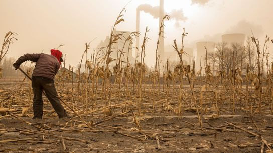 A farmer prepares for spring near a power plant in Shanxi Province, China. The facility, which ...
