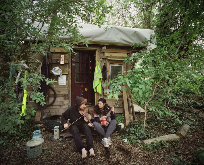 A couple sits in front of their home in the wooded area of Grow Heathrow. He ...