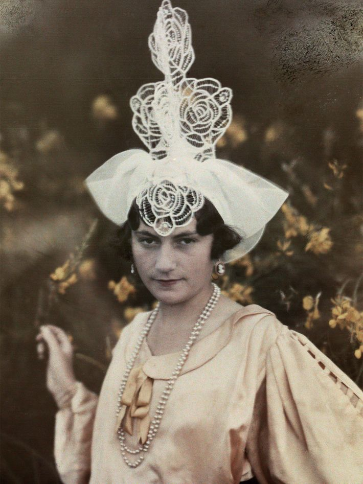 A young woman from Les Sables D'Olonne, France, wears a towering headpiece with the shapes of ...