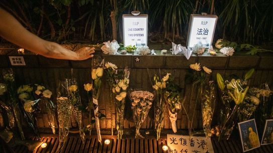 A woman lights a candle at a makeshift memorial in Hong Kong commemorating the death of ...