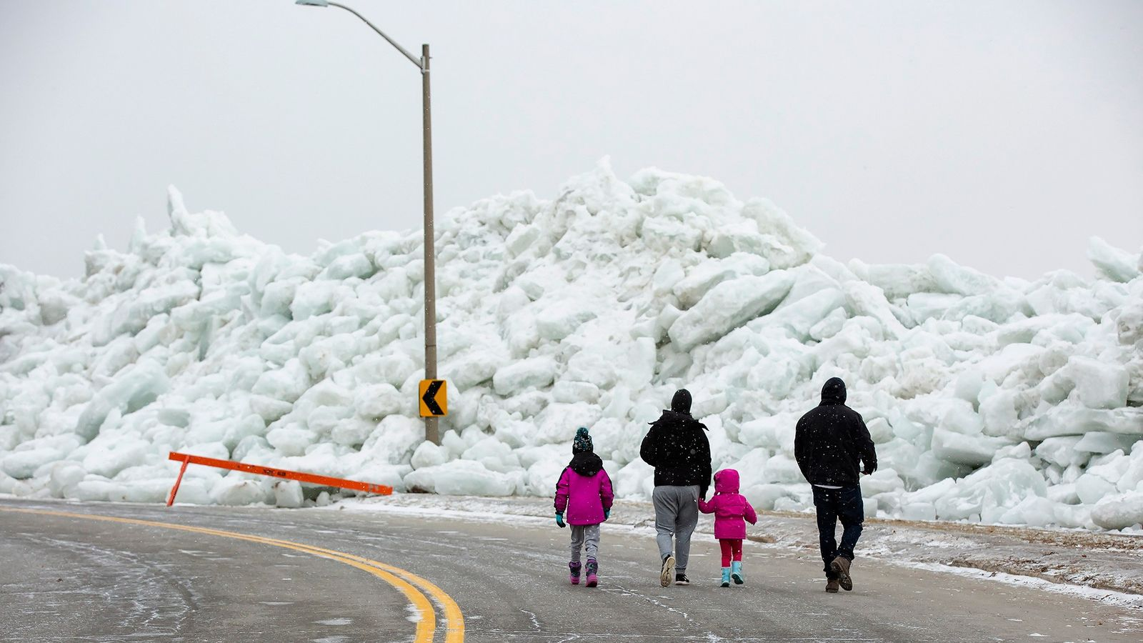 A family walks near a massive buildup of ice pushed onto the shore of Mather Park ...