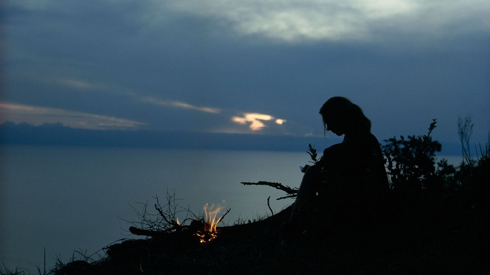 The sun's fading glow on Lake Tanganyika silhouettes the author, who is preparing for a lonely, ...