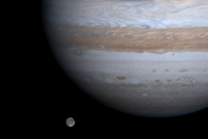 The solar system's largest moon, Ganymede, seems to float alongside Jupiter in a picture taken by ...