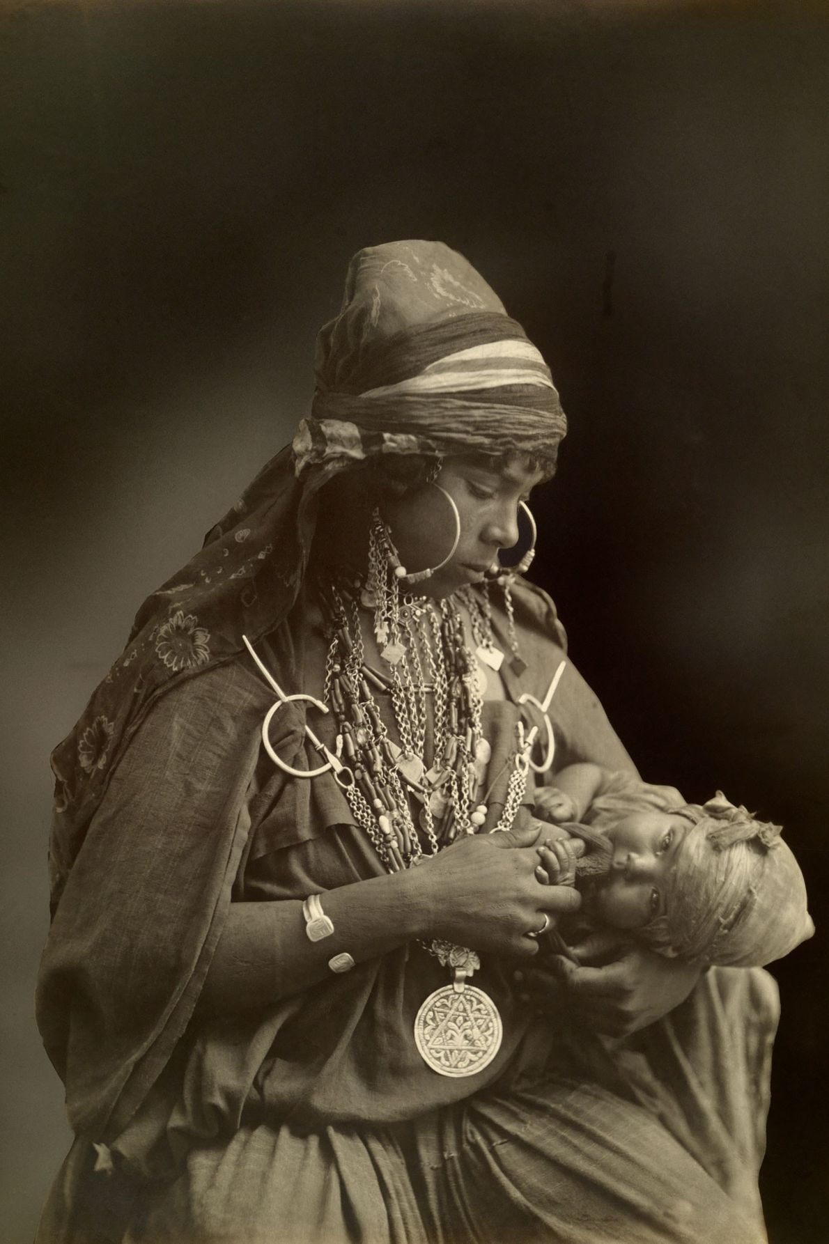 A Bedouin mother, elaborately adorned with jewelry, gazes at her infant child in the early 1900s.