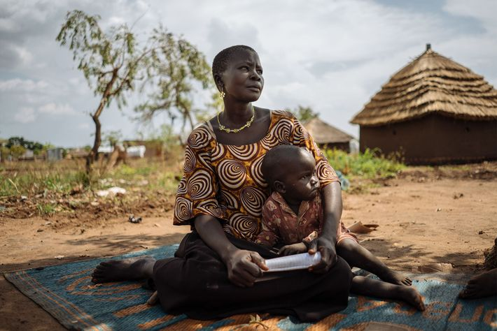Emaleda, a woman from South Sudan, sits on a mat with her child near their home ...