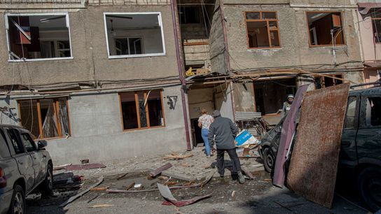 Residents of Stepanakert, the capital of the self-declared Nagorno-Karabakh Republic, enter a building damaged by a ...