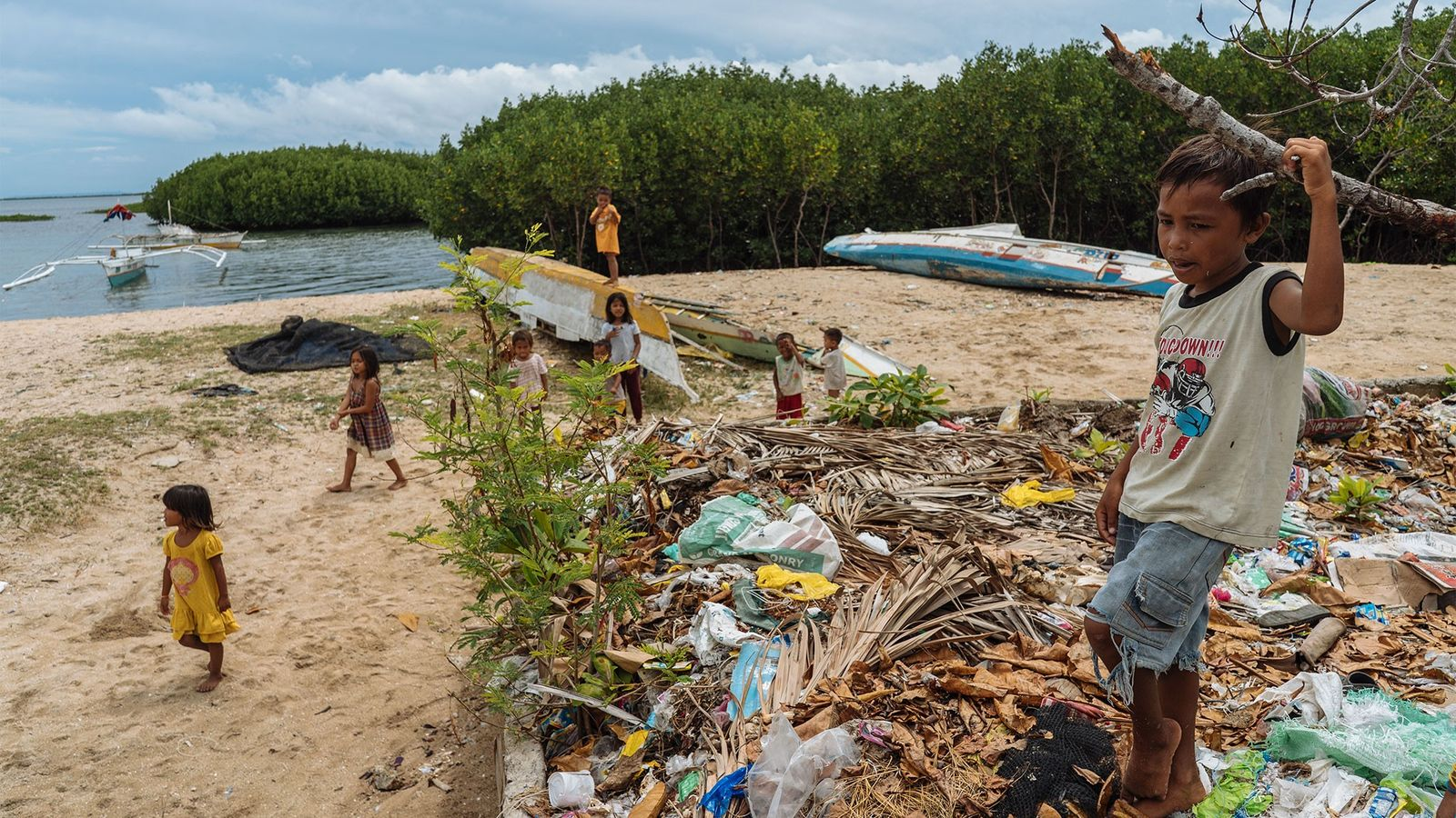 Children play by a dumping area in Bohol, Philippines. During high tide and rains, the waste ...