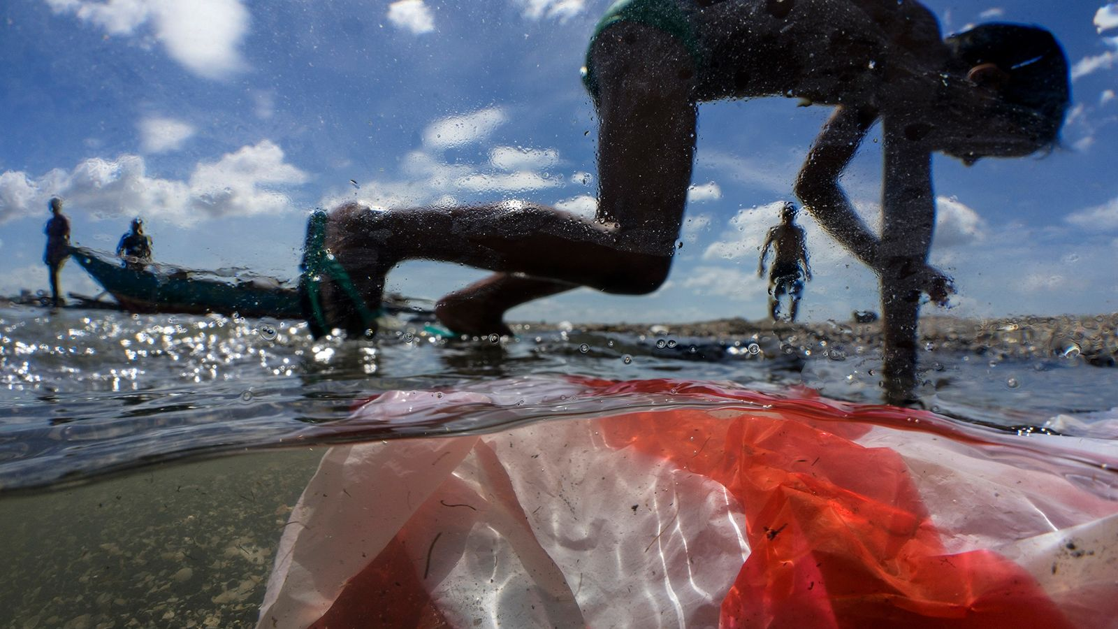 Children play on the shore of Manila Bay, which is polluted by household waste, plastics, and ...