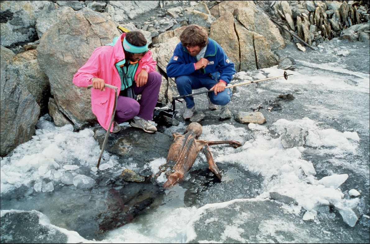 Mountainer Reinhold Messner, right, and colleague inspect the mummified remains of Ötzi the Iceman following his ...