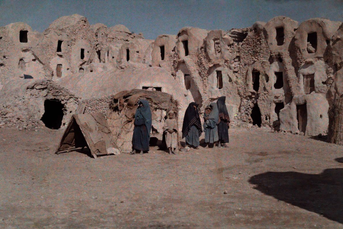 Residents stand in front of cave dwellings in Matmata, Tunisia.