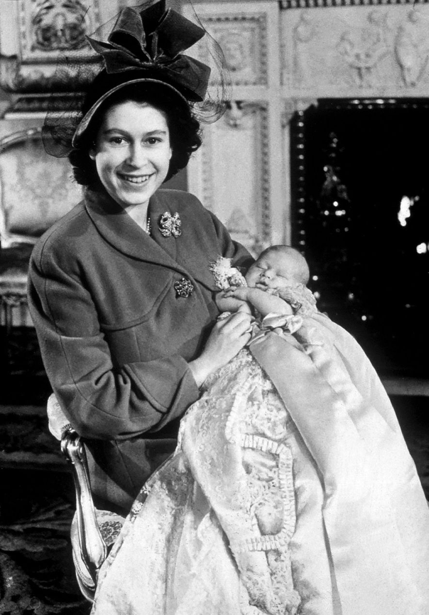 Queen Elizabeth II holds Prince Charles, her first child, at his christening in 1948, prior to ...