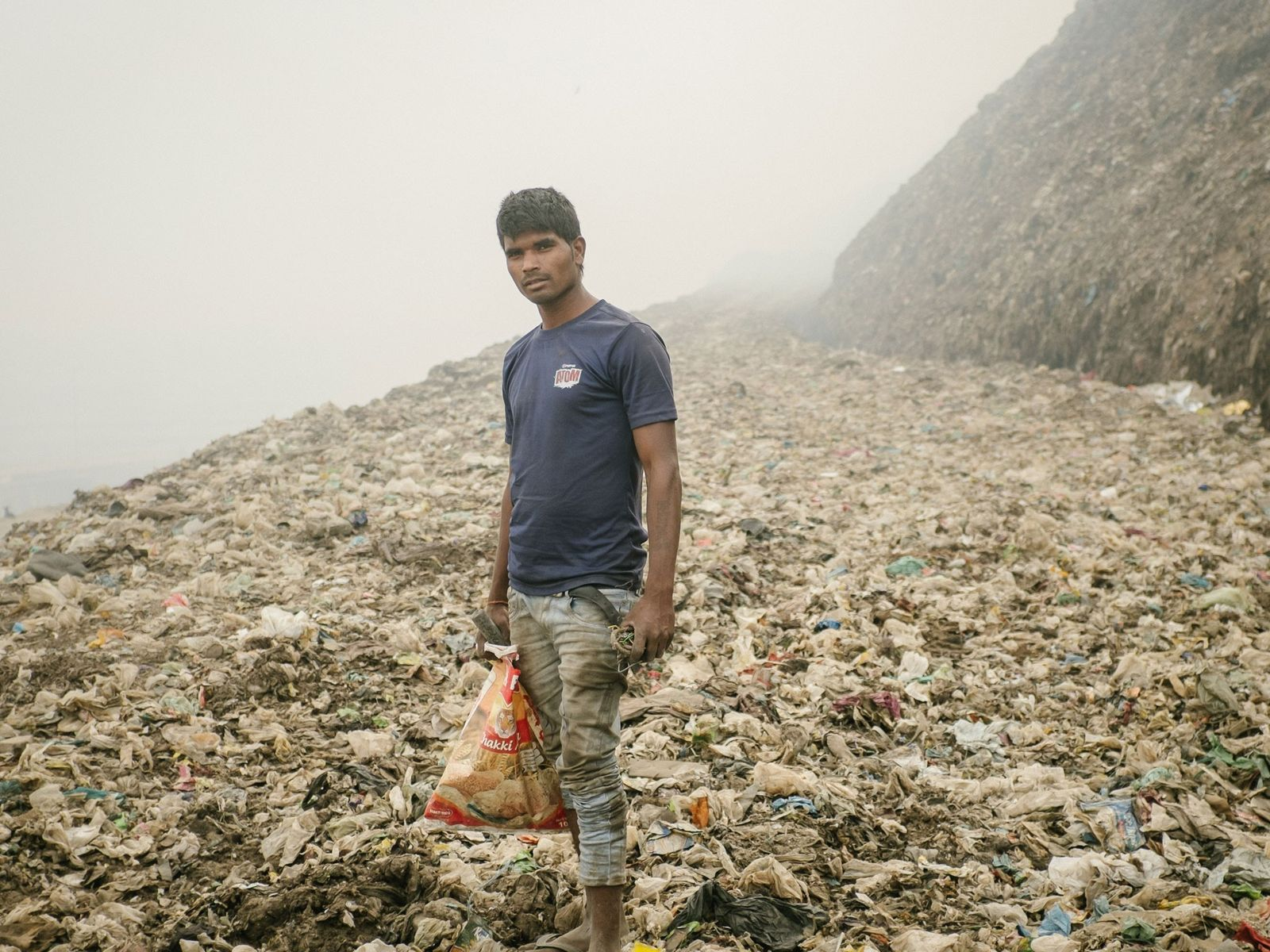 A recycler looks for metal in Bhalswa, a giant garbage dump that burns constantly, emitting toxic ...