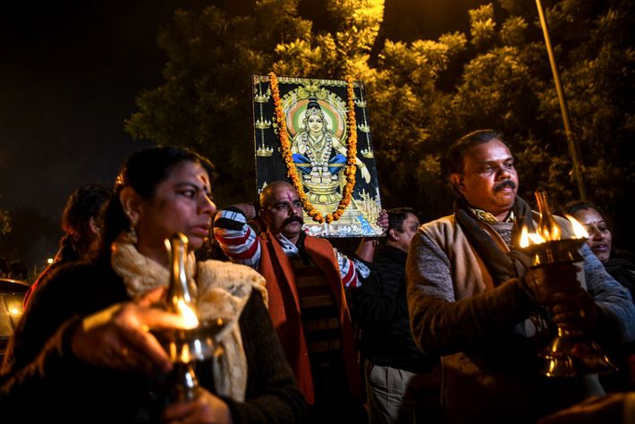 Supporters of the traditional ban against reproductive-age women at the Sabarimala temple hold a candlelight vigil. ...