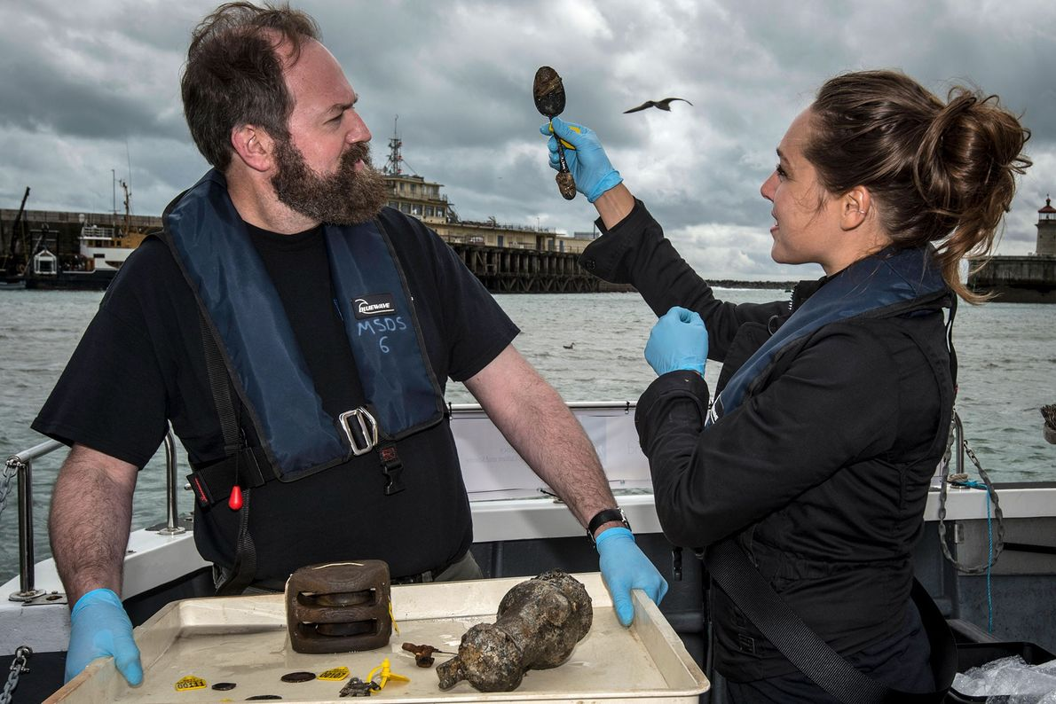 Conservation team members Elisabeth Kuiber and Eric Nordgren with finds including a spoon from the Rooswijk ...