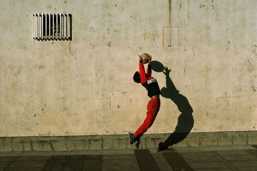 During a schoolyard football game in Tokyo, Japan, a goalie jumps and extends his arms to ...