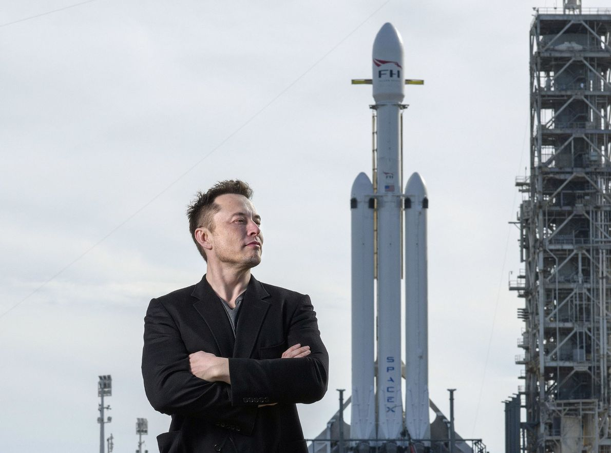 Elon Musk, founder of SpaceX, poses with the company's Falcon Heavy rocket at Launch Pad 39A ...