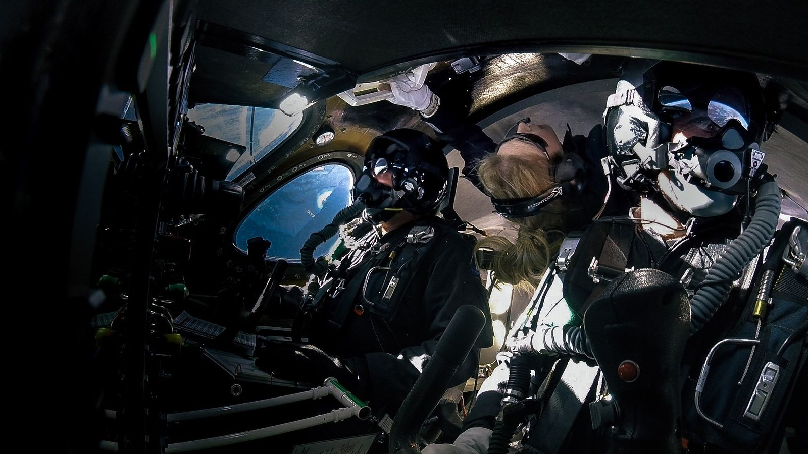 Beth Moses (center) floats in microgravity on board a Virgin Galactic flight on February 22.