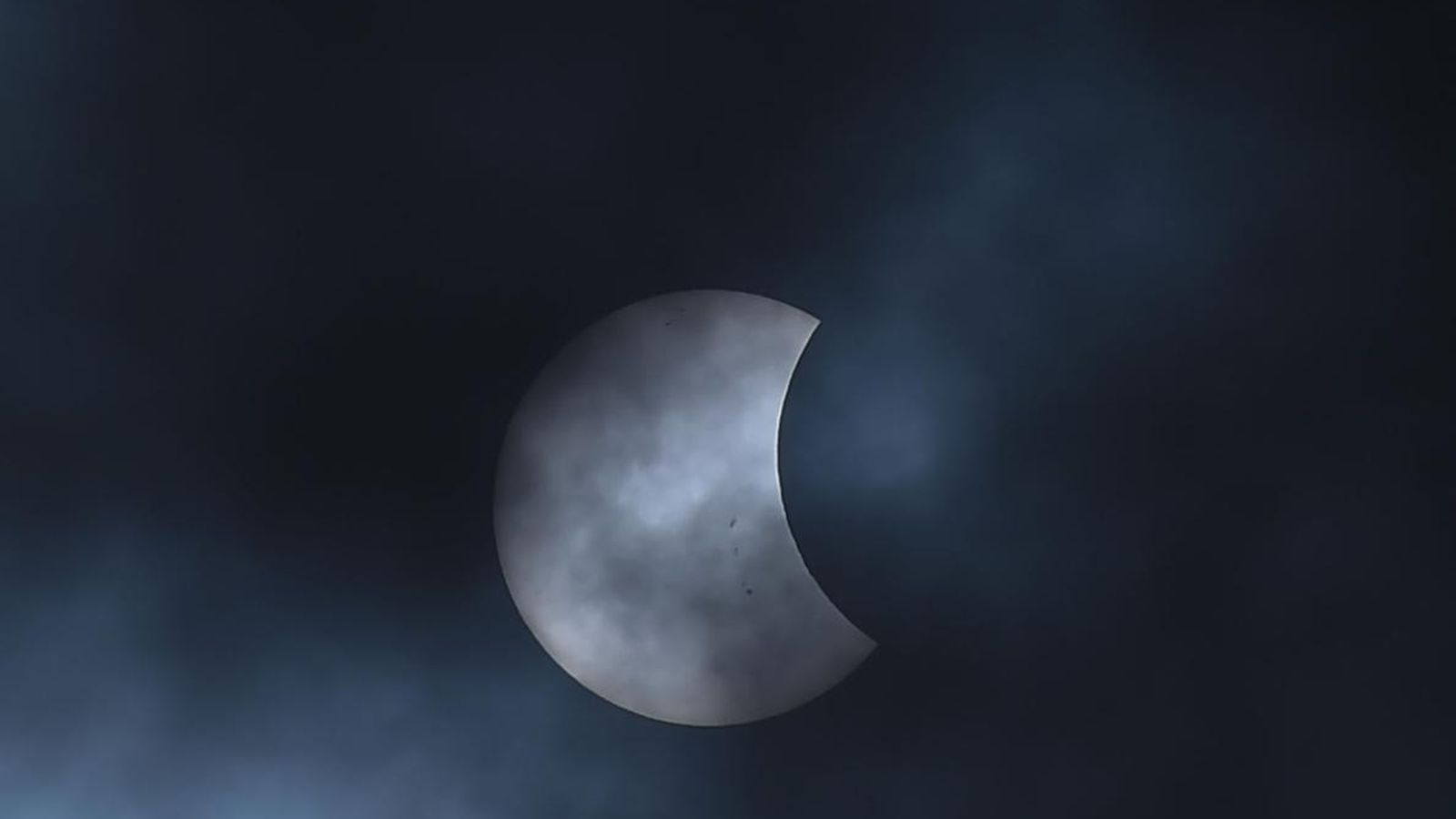 The moon glides in front of the sun during a partial solar eclipse seen from Bogotá, ...