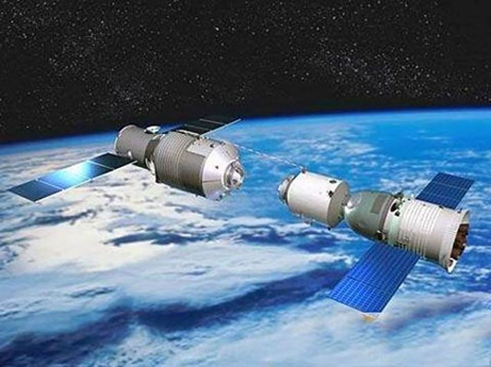 A crewed space capsule docks with the Tiangong-1 space station in an illustration released by Chinese ...