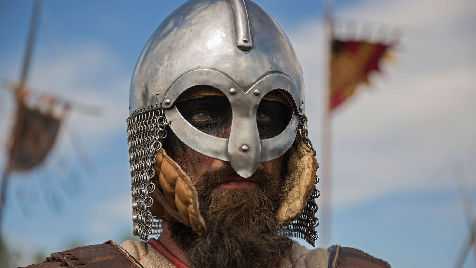 A Viking reenactor in full Viking dress stands at a festival in Poland.