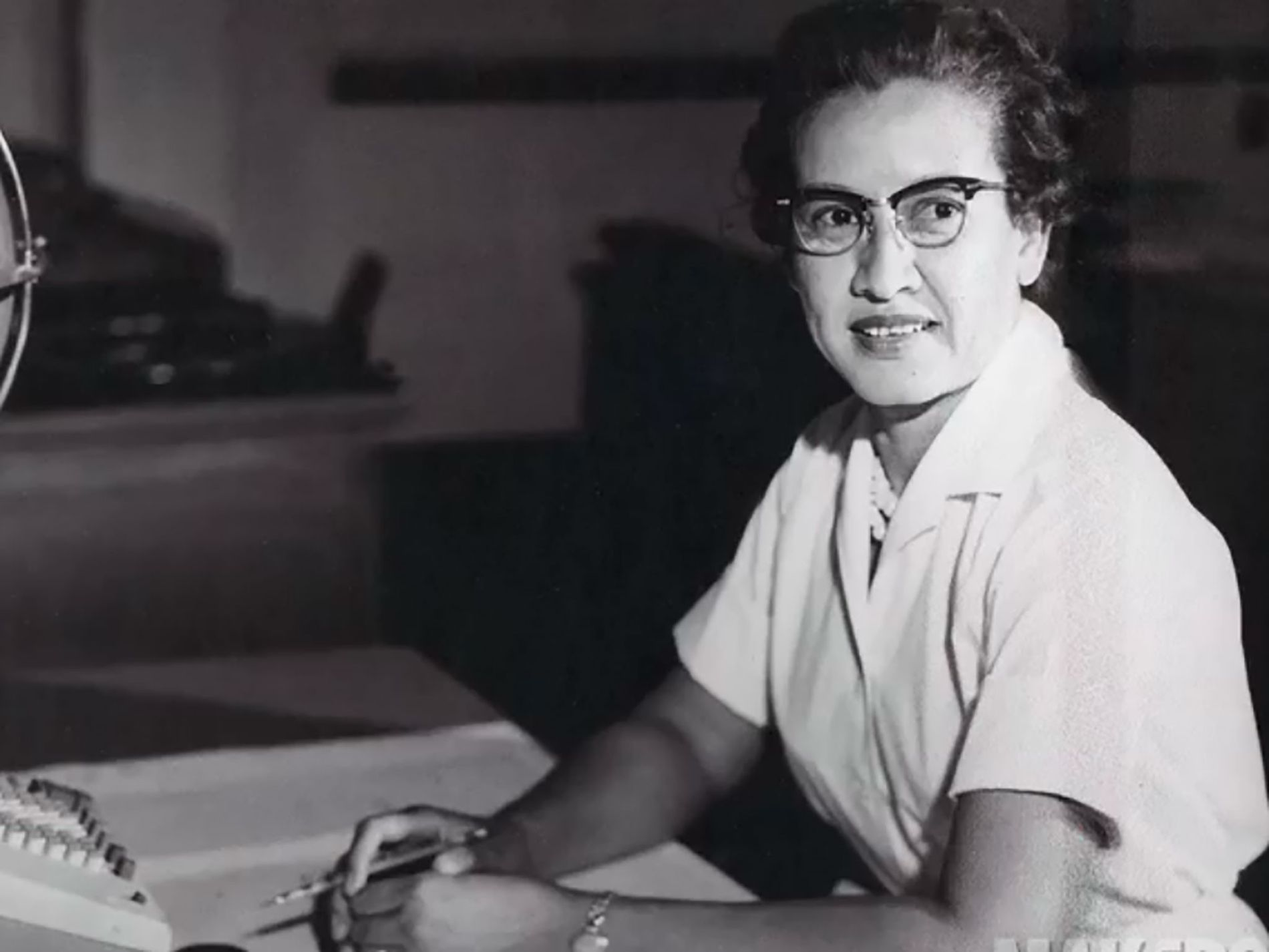 "NASA research mathematician Katherine Johnson is photographed at her desk at NASA Langley Research Center with a globe, or ""Celestial Training Device."""