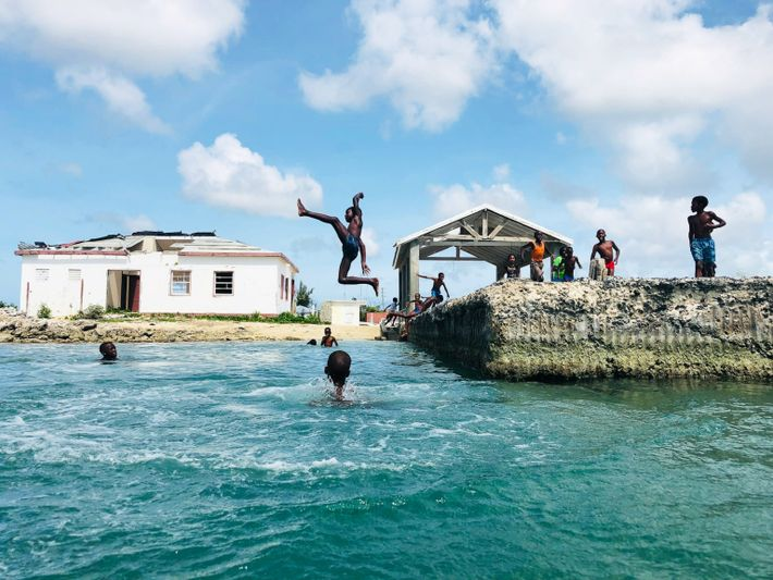 Children jump off the wharf into the Codrington Lagoon in Barbuda. Barbudans have participated in activities ...