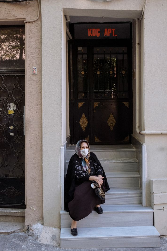 A woman in a mask takes a smoke break in Istanbul. Rolling curfews and lockdowns have ...