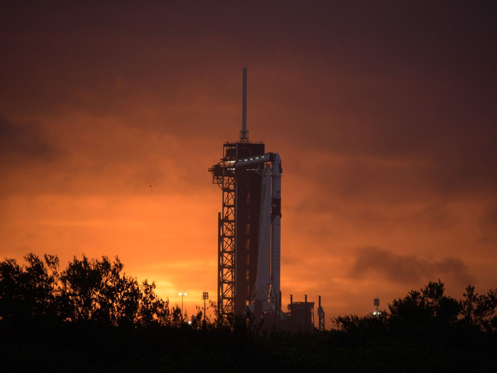 The SpaceX Falcon 9 rocket and Crew Dragon spacecraft perch above Launch Complex 39A at Florida's ...