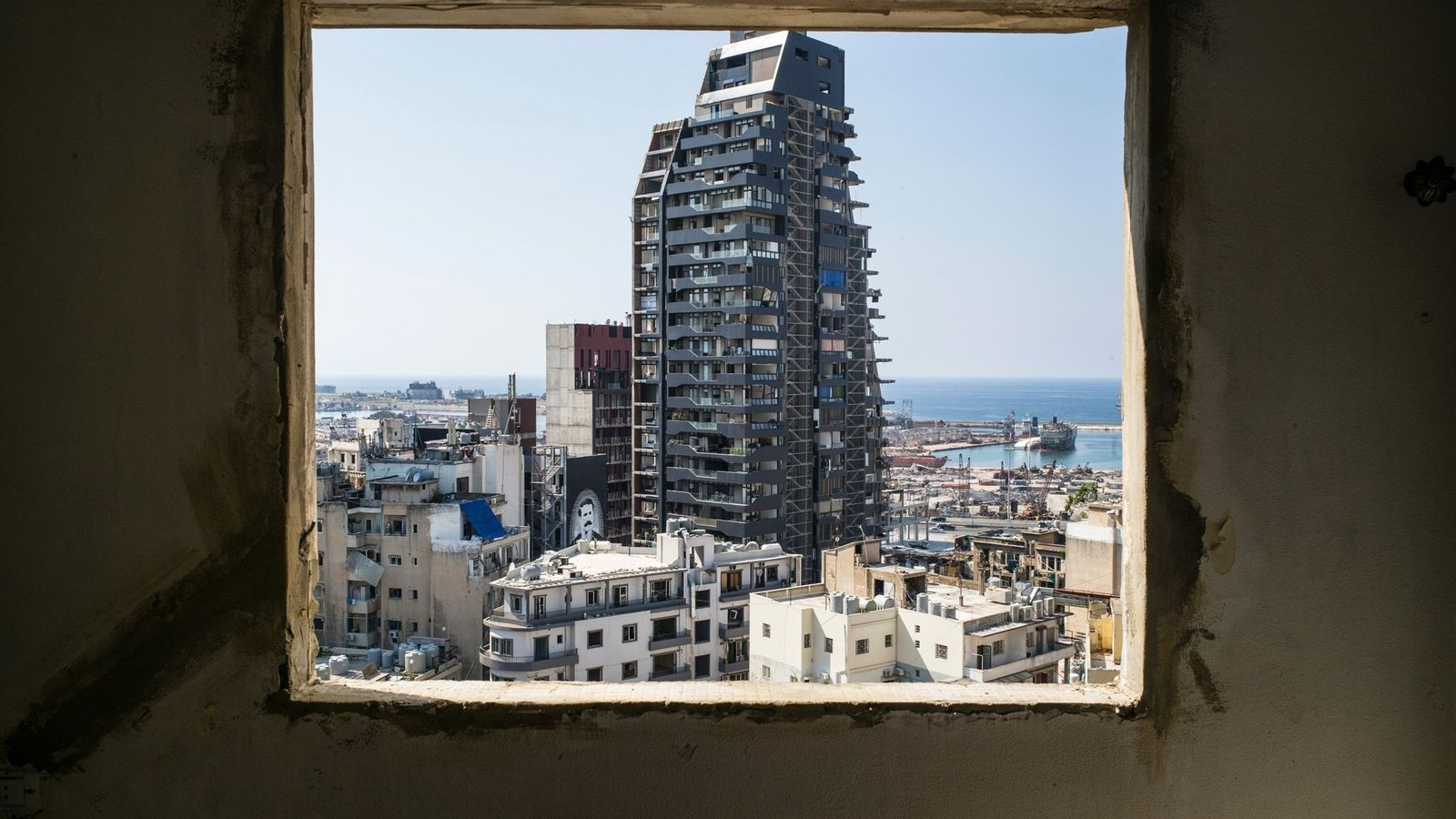A window of a damaged house in the Geitawi neighbourhood of Beirut, Lebanon, frames a view ...
