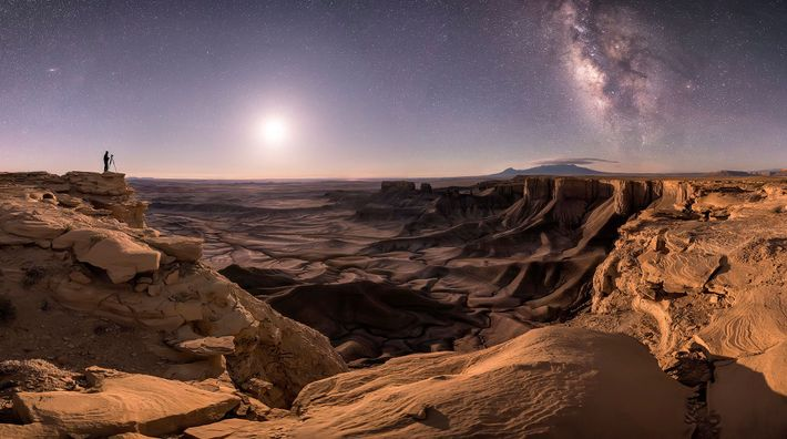 A lone photographer stands in Moab, Utah, silhouetted against a night sky that reveals the Andromeda ...
