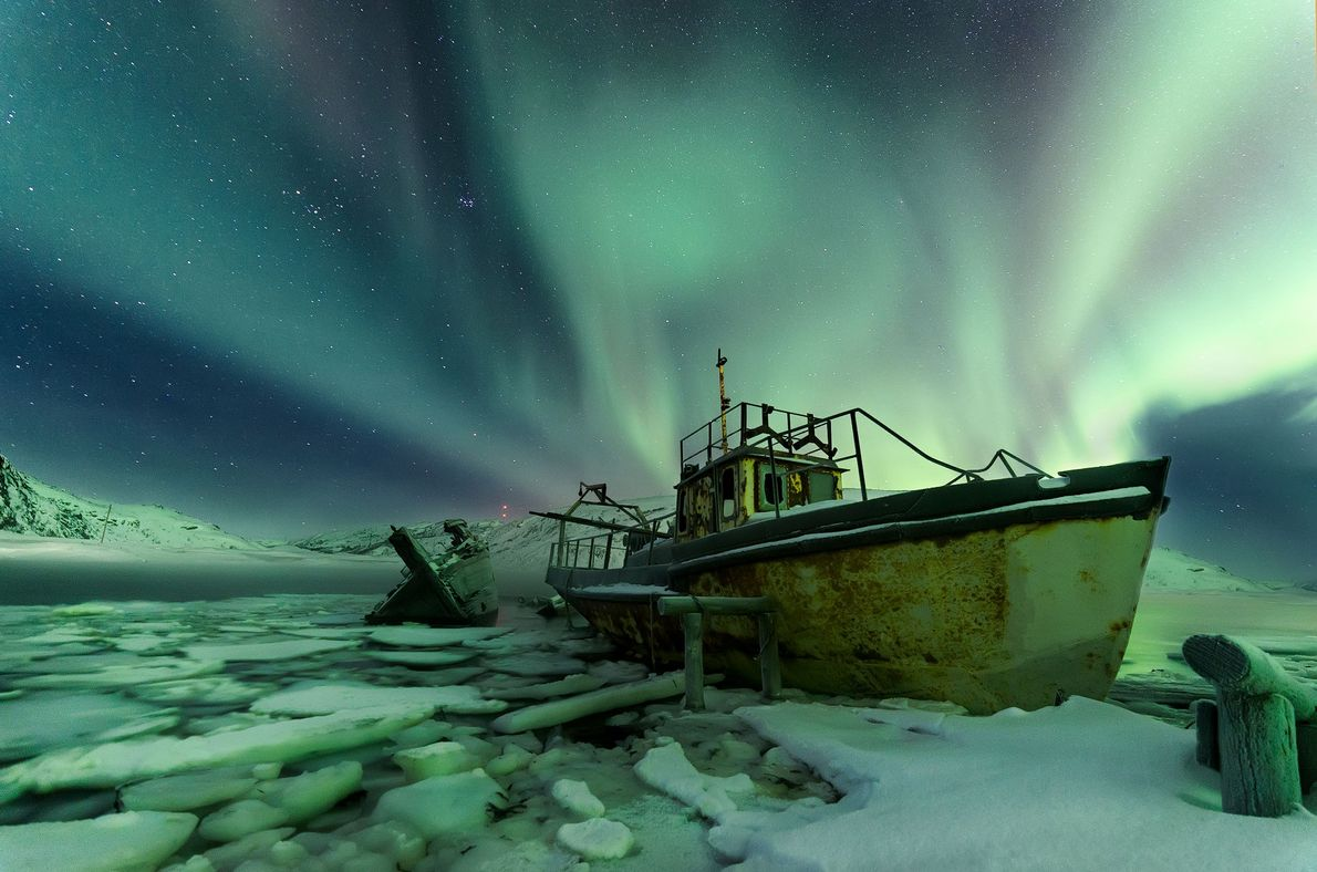 The northern lights glow behind old, abandoned ships in the village of Teriberka, Russia. Once a ...