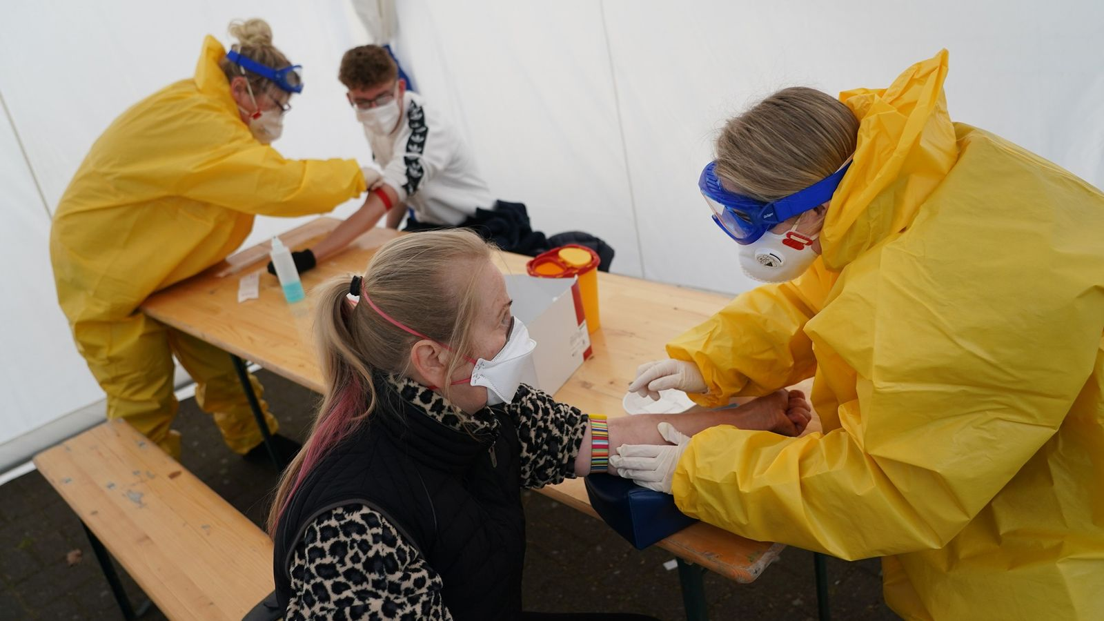 Medical volunteers dressed in protective suits, masks, gloves and goggles take blood samples from visitors with ...
