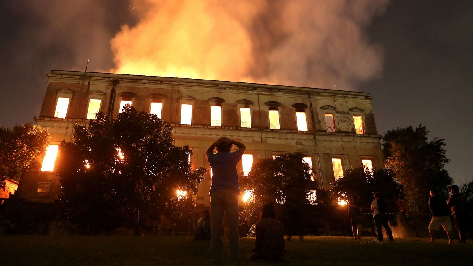 People watch as a fire burns at the National Museum of Brazil in Rio de Janeiro ...